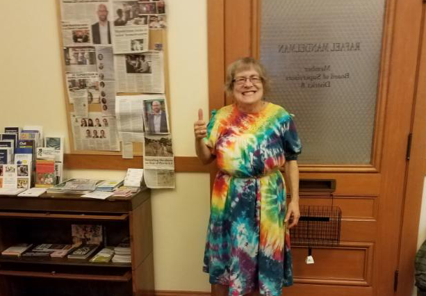 woman in a tye dyed dress with a thumbs up