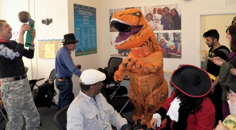 dinosaur in office with staff in costumes