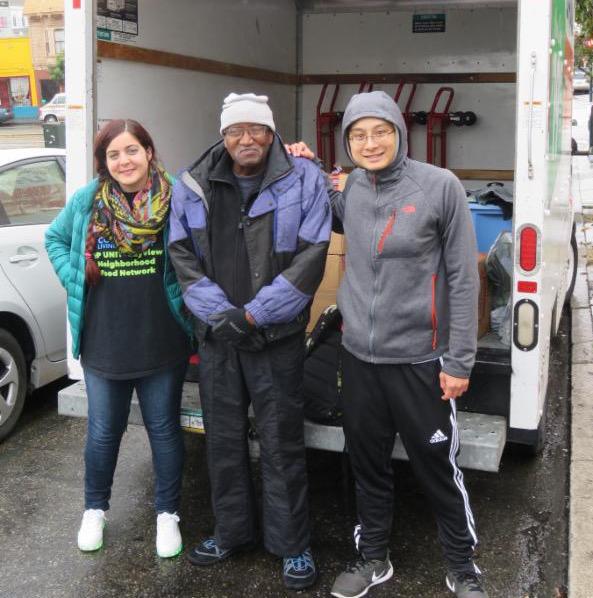 three volunteers in front of truck