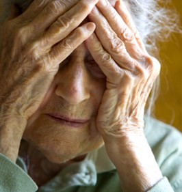 older woman with hands on head looking worried