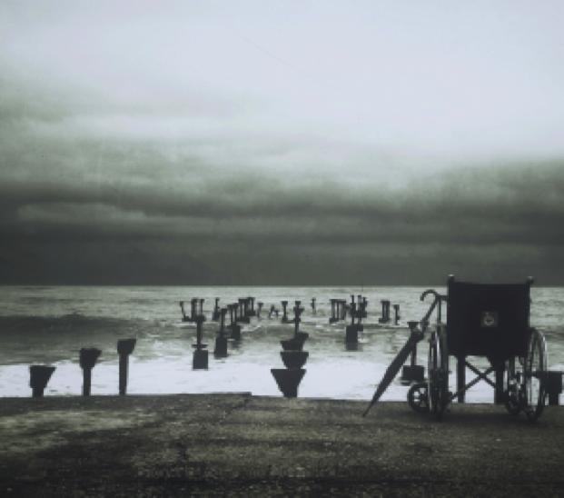 wheelchair at the edge of a broken pier