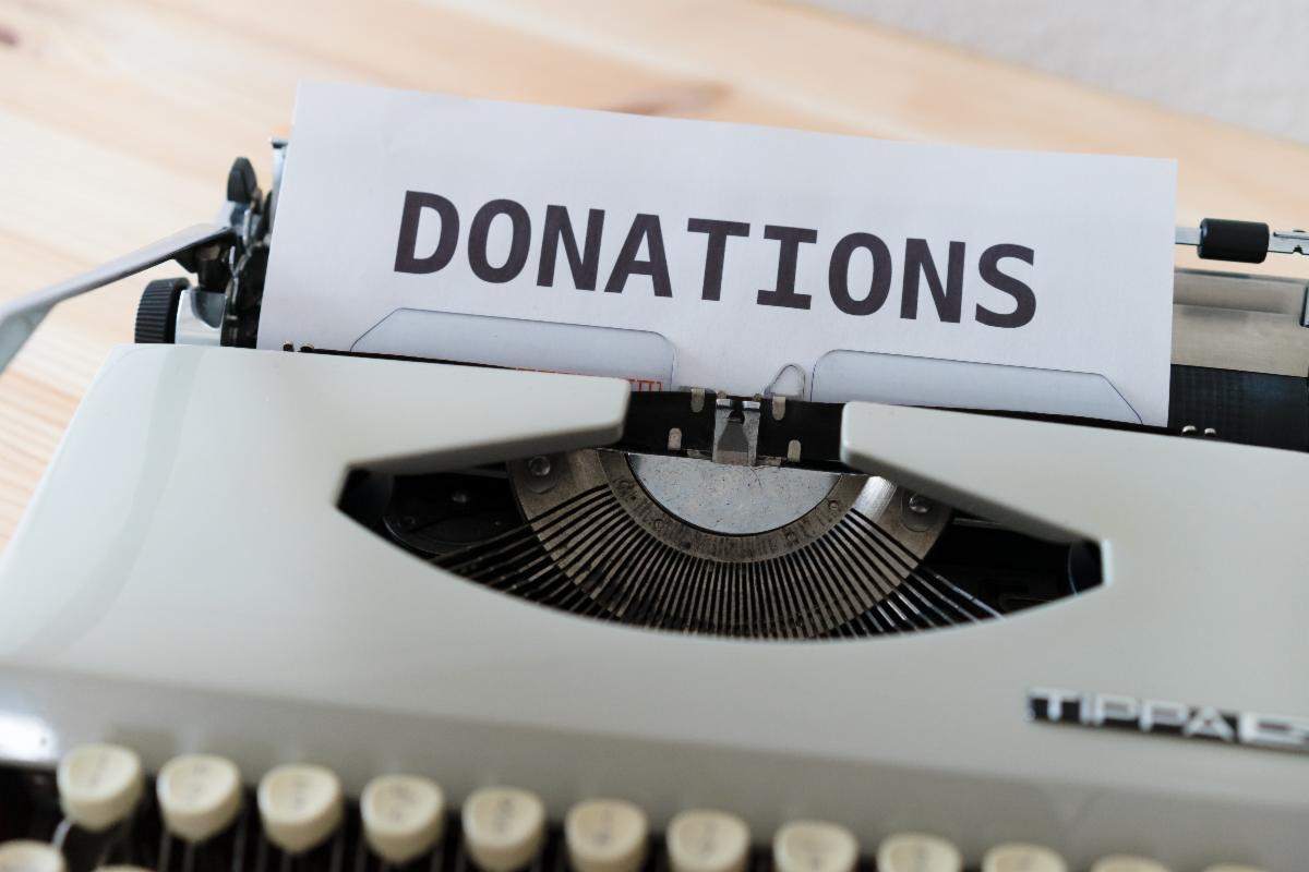 Typewriter with Donations in black letters typed on white paper