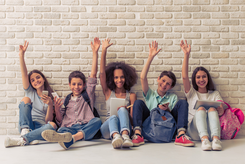 Group of teenage boys and girls is using gadgets_ keeping hands up_ looking at camera and smiling_ sitting against white brick wall