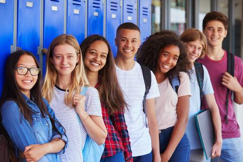 Teenage school kids smiling to camera in school corridor