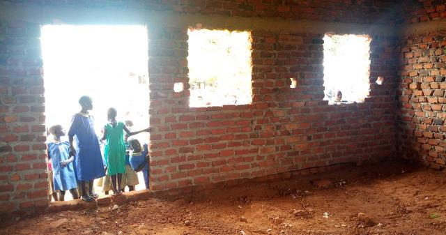 Students in Uganda stand outside a pre-renovated school room.