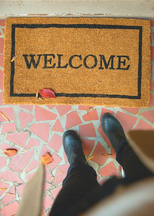 Person standing in front of a Welcome Mat