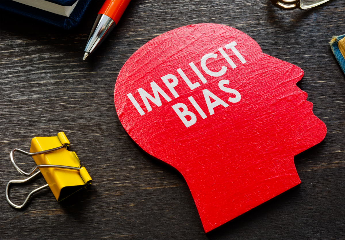 Image of implicit bias written on a head cutout.
