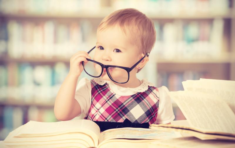 Baby girl with glasses and books.