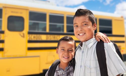 Young Hispanic Boys Walking Near School Bus.