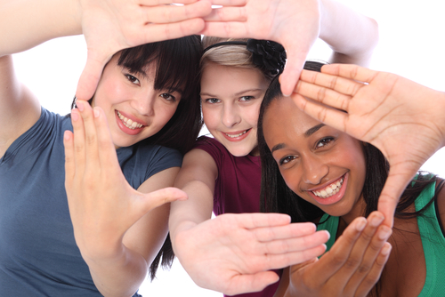 Fun hand sign by three multi cultural teenage school student friends made up of mixed race african american_ oriental Japanese and caucasian all happy holding hands out to camera.