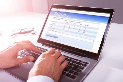 Close-up Of A Businessman s Hand Filling Online Survey Form On Laptop