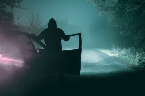 A lone_ hooded figure standing next to a car looking at an empty misty winter country road silhouetted at night by car headlights. With a cold_ grainy_ muted edit.