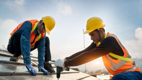Two construction men working on top of building