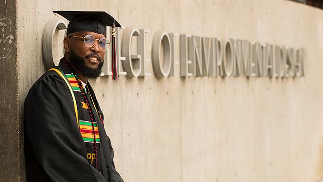 Corey Norman posing in front of Bldg 7 in graduation regalia