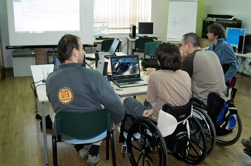 Four people using wheelchairs working on computers