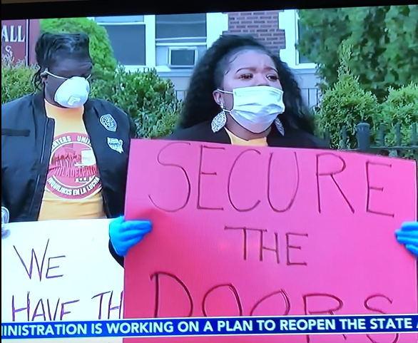 Renters hold signs at a socially distant protest
