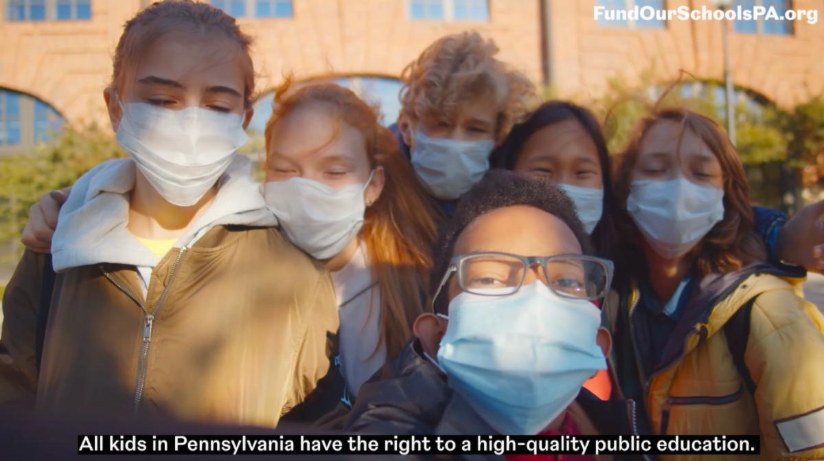 Kids wearing face masks outside a school, smiling