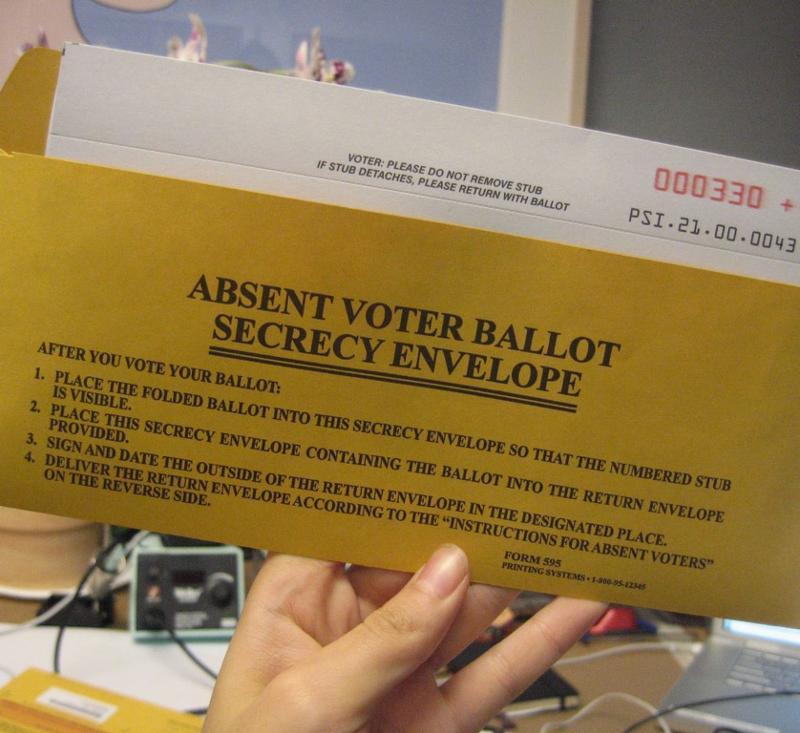 A hand holding an absentee ballot envelope