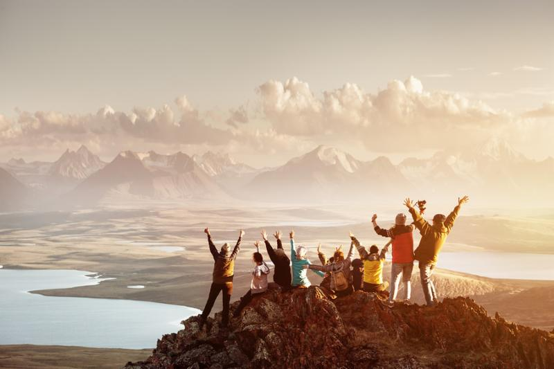 Big group of people having fun in success pose with raised arms on mountain top against sunset lakes and mountains. Travel_ adventure or expedition concept