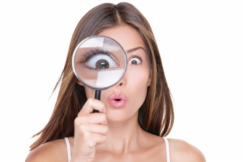 Funny expression. Shocked woman looking through a magnifying glass. Surprised Asian girl looking astonished discovering clues with big eyes through a magnifying glass_ isolated on white background.