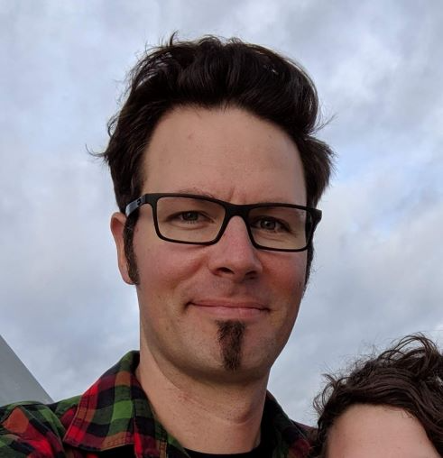 A headshot of Andrew Petitdemange wearing glasses and a red flannel shirt.