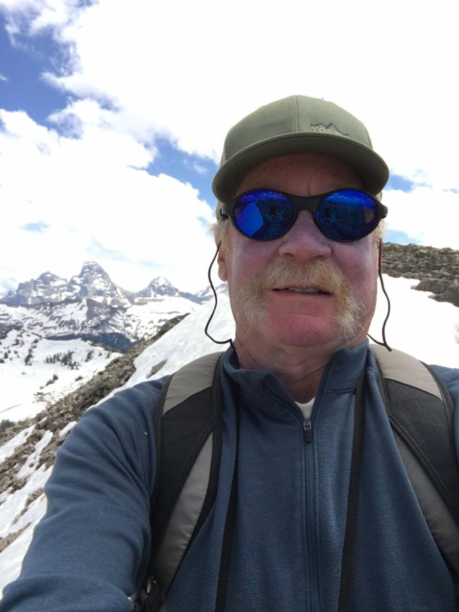A selfie of Dan Bowler at the top of Targhee Ski Resort with Grand Teton in the background.