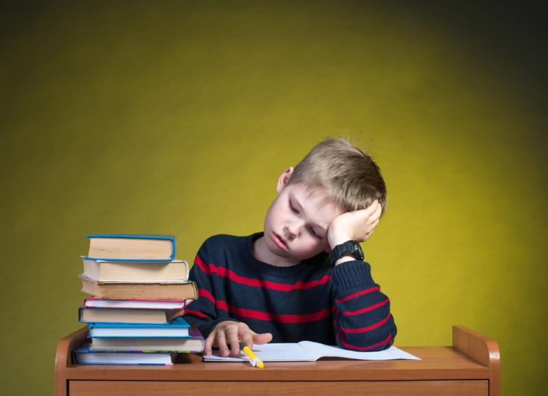 Photo of young boy looking frustrated and seated at desk with stack of books and homework on desk