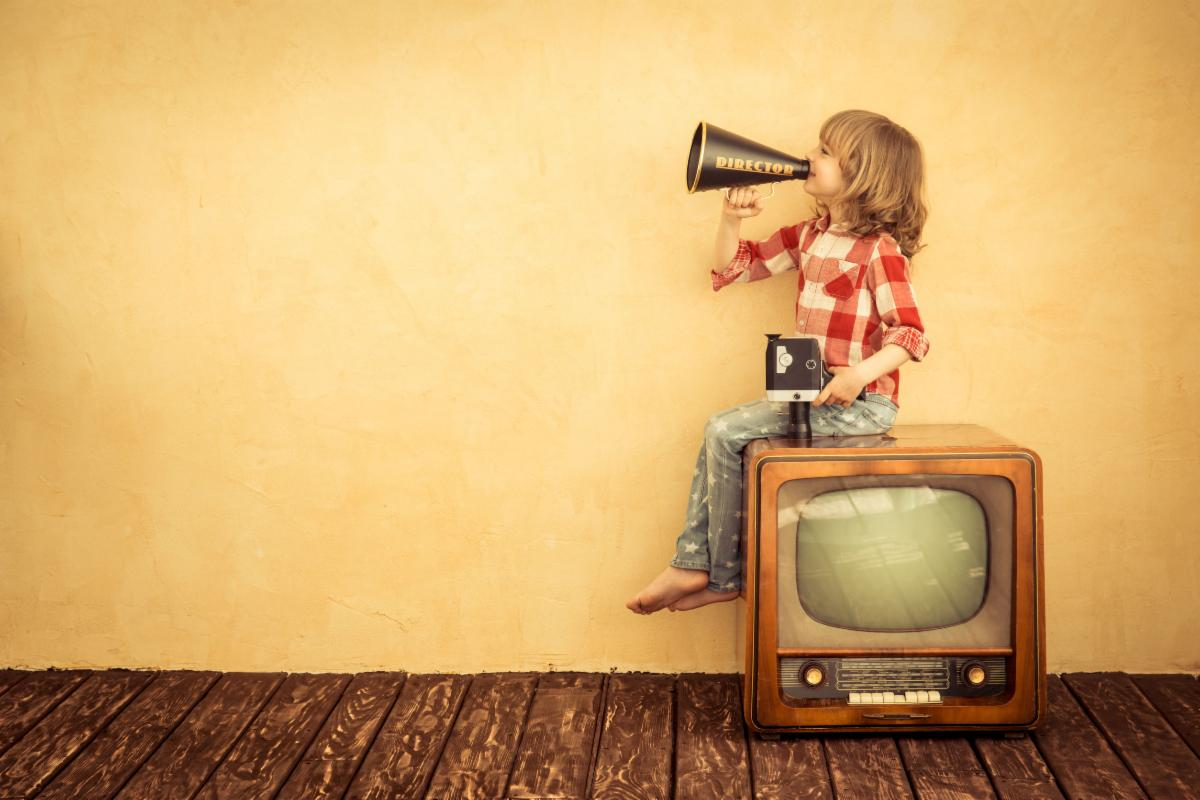 child with megaphone on vintage tv