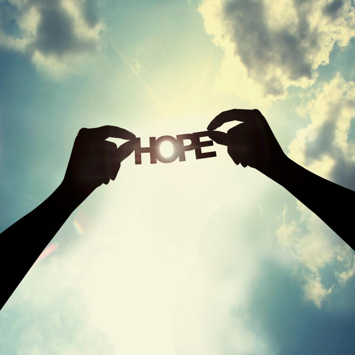 outline of word HOPE against bright sun