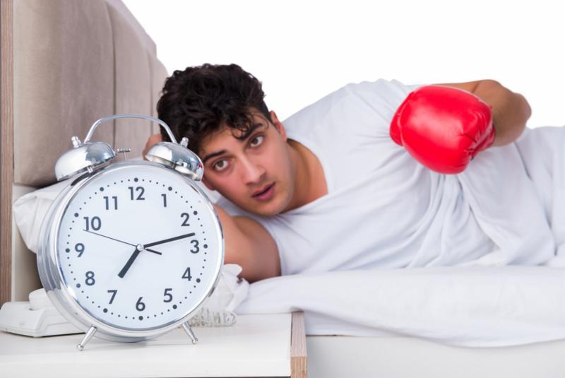Man in bed punching alarm clock