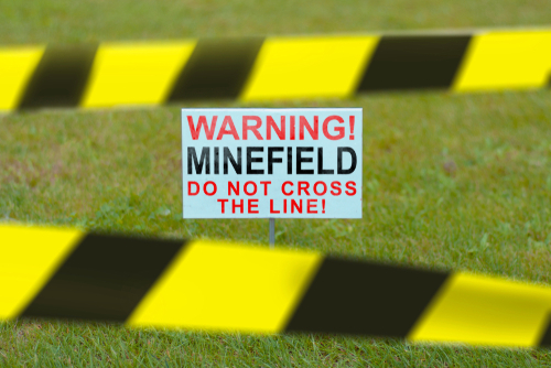 The sign on the lawn with the inscription WARNING  MINEFIELD DO NOT CROSS THI LINE closed prohibitory tapes