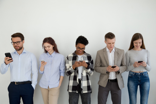 Millennial phone users business people group standing in row using smartphones_ diverse customers holding cellphones looking on gadget waiting in line_ mobile addiction social media lifestyle concept