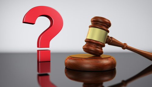 Law and legal questions concept with a red question mark sign and a wooden judge gavel on a desk with grey background 3D illustration.
