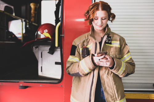 Photo of young woman firefighter with phone in her hands against background of fire engine