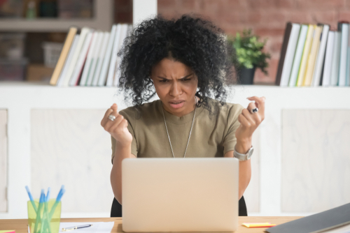 Angry african American millennial woman get annoyed using laptop having software problem_ mad black female witness computer virus attack or spam_ furious biracial girl experience device breakdown
