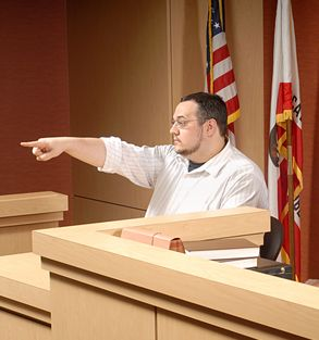 Man acting as a witness pointing out someone to the judge