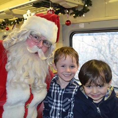 Santa Claus poses for a photo with two young boys.