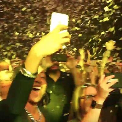Party-goers celebrate as confetti falls around them.
