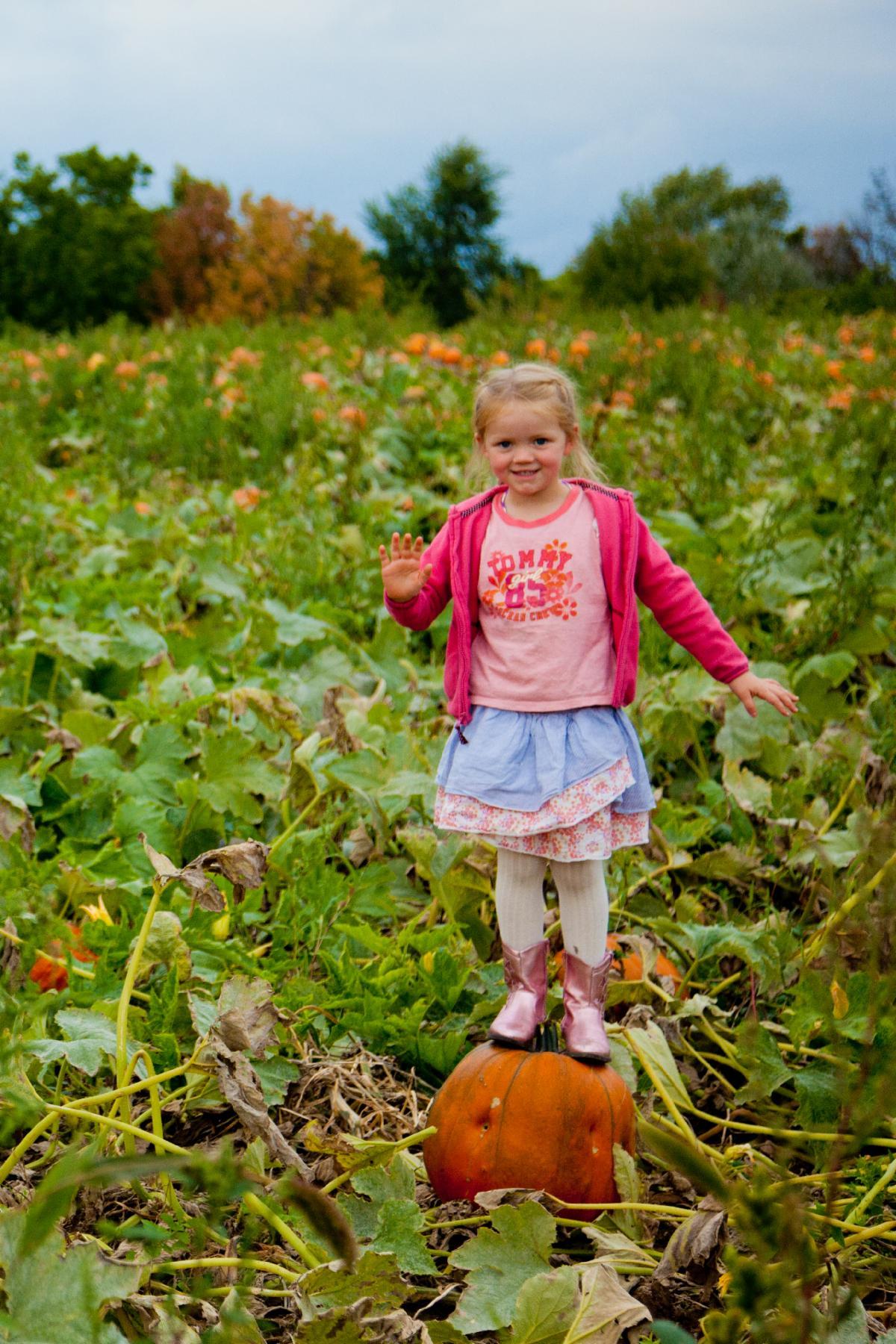 Girl standing on pumpkin