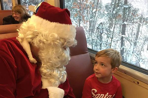 Santa Claus speaks with a young boy.