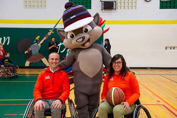Two para-athletes pose with PACHI the Ontario Parasport Games mascot.