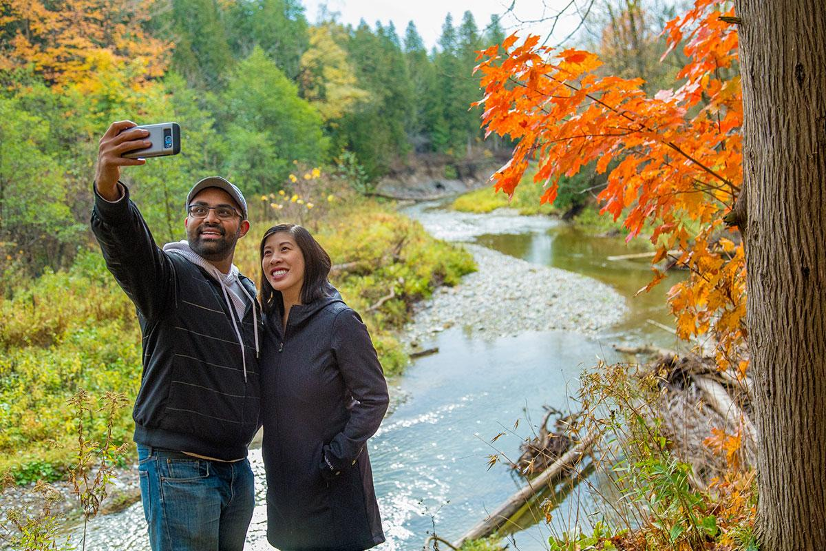 Man and woman taking selfie on trail