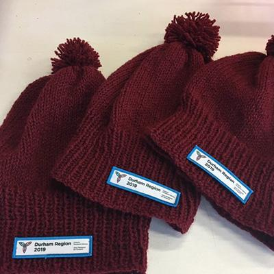 Three knitted red toques with Durham Region 2019 Ontario Parasport Games logo.