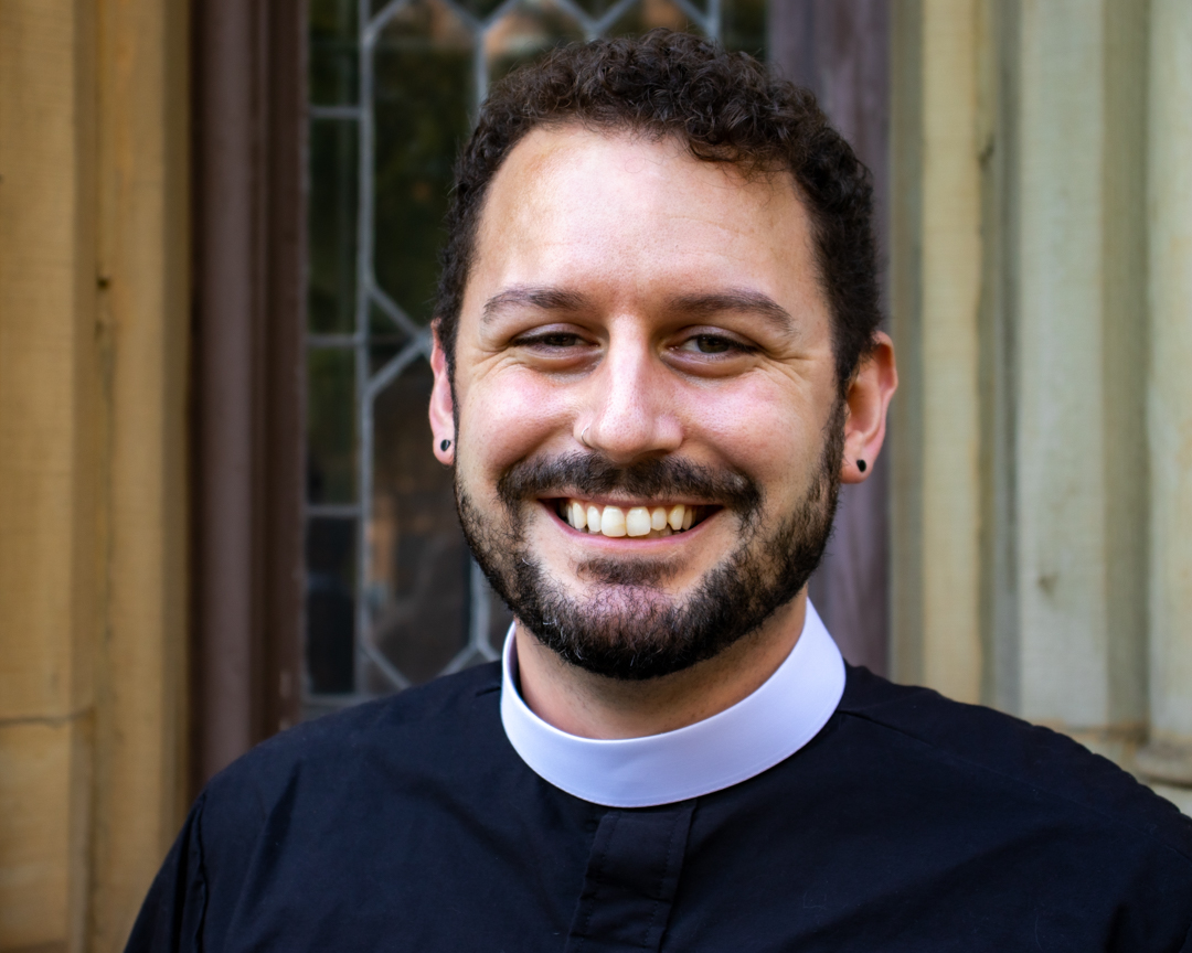 Pastor Lance Hurst, a white young adult with a large smile, a brown beard and brown hear, wearing a clergy collar and starting in front of the door of FPC of Glen Cove.