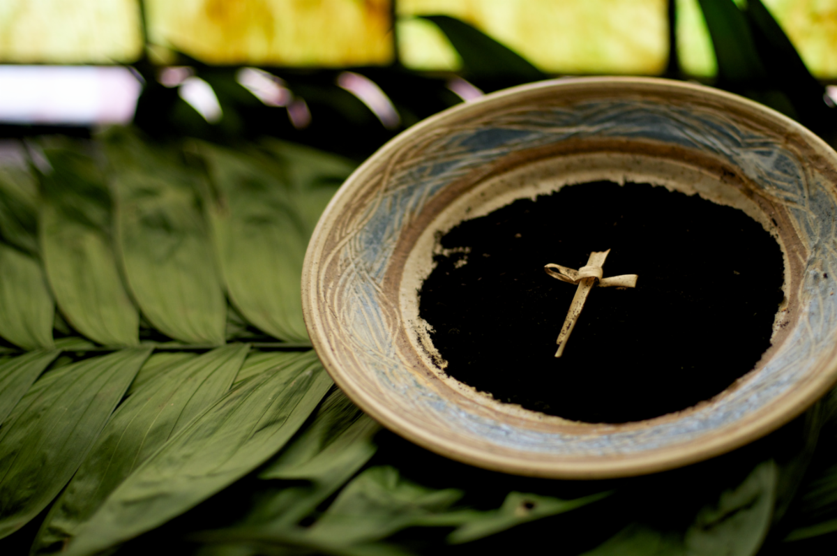 In this photo are both palm leaves and a bowl of ashes made from palm leaves. In the middle of a bowl is a handmade cross.