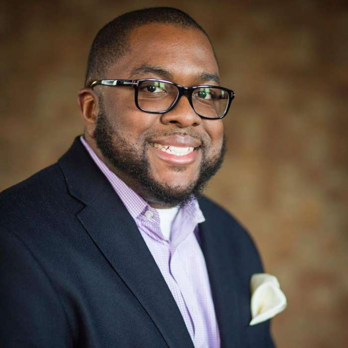 A photo of Dr. Kirk A. Johnson (he/him/his), an African-American male professor wearing glasses, a black suitjacket, and a purple button-up shirt. He is smiling and sitting, angled toward the camera, against a brown and white background.