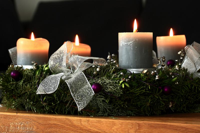 Advent wreath with four burning candles on a table