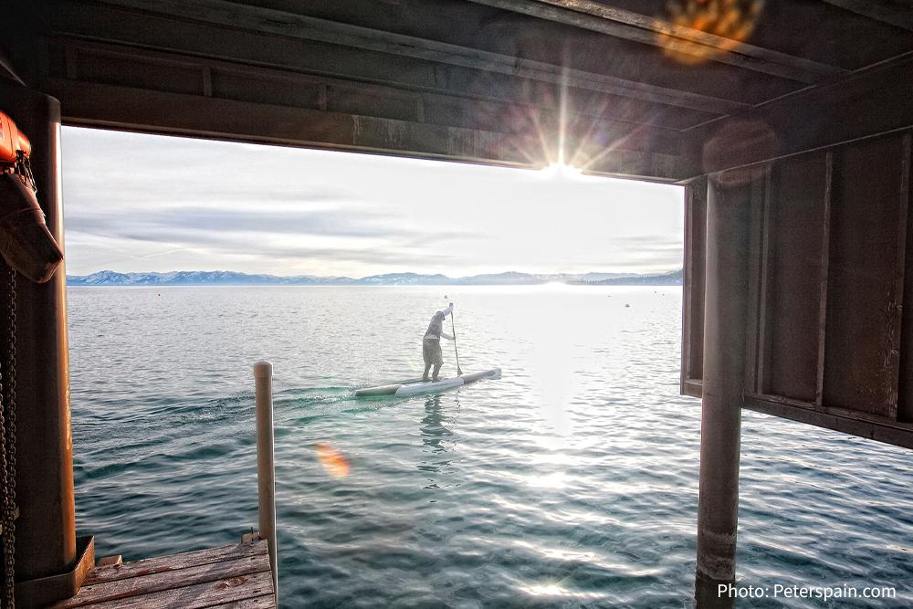 Paddle boarder under pier at Tahoe