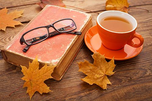 Book, cup of tea, and fallen leaves