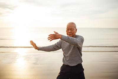 Man doing tai chi by the ocean
